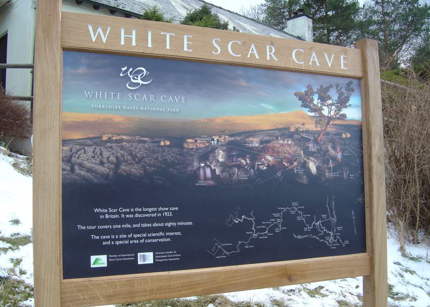 Visitor attraction entrance sign with routed oak wood header panel, lettering paintedpanel;
