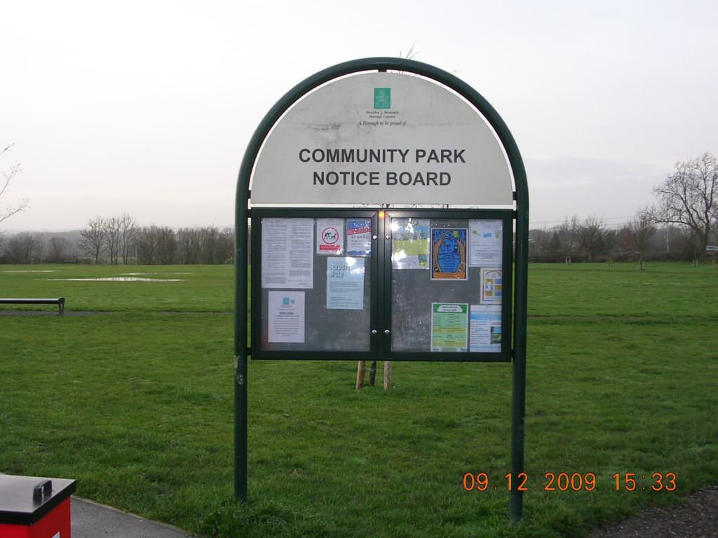 A lockable notice board in an urban park. Set in a tubular steel frame and with a printed header panel. Notice board is hinged & lockable.