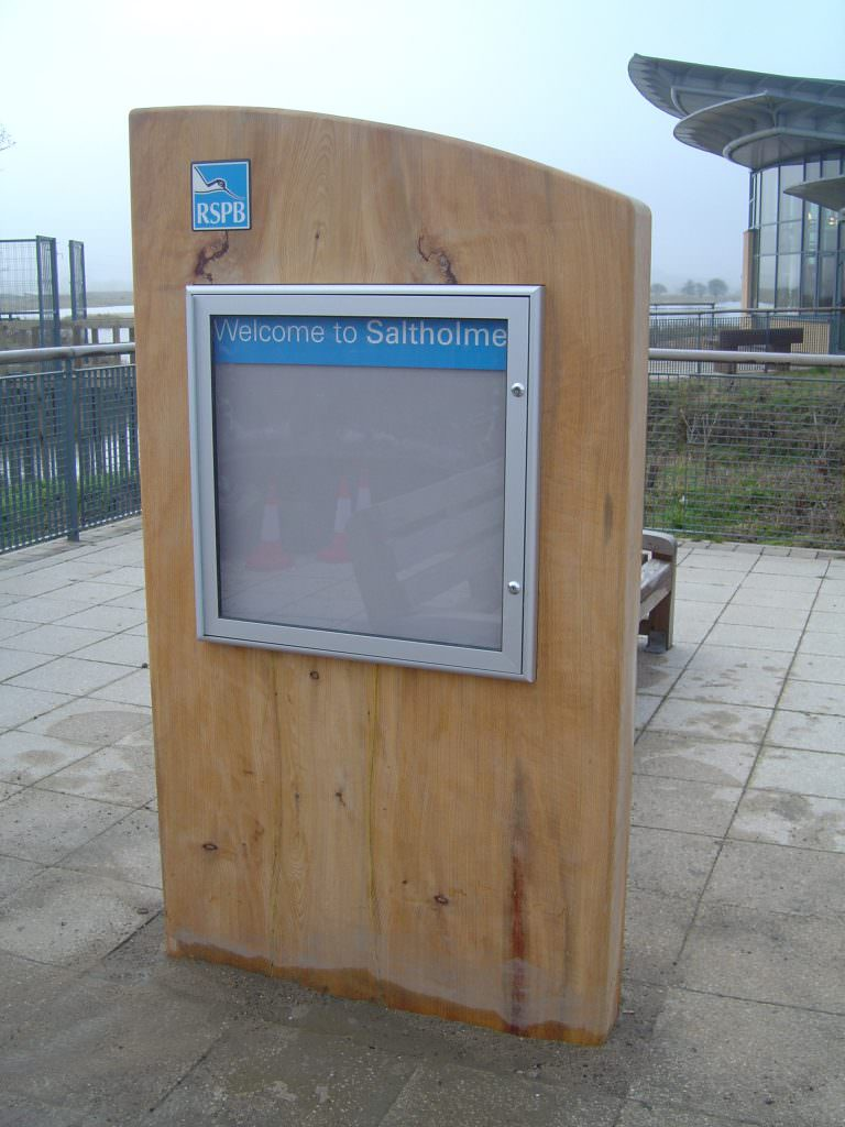 An aluminium notice board, hinged & lockable and mounted on a large section of Cedar with routed text on the top.