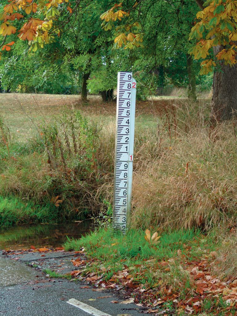 A single post mounted D50 gauge board reading from 0 to 2m. Supplied with red datum numerals and by the edge of a stream & ford in a road