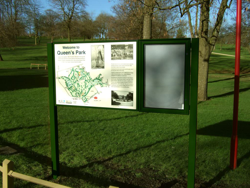 A historical based information panel explaining the history of Queens Park in Bolton. Board set in a vertical metal frame with a lockable notice board