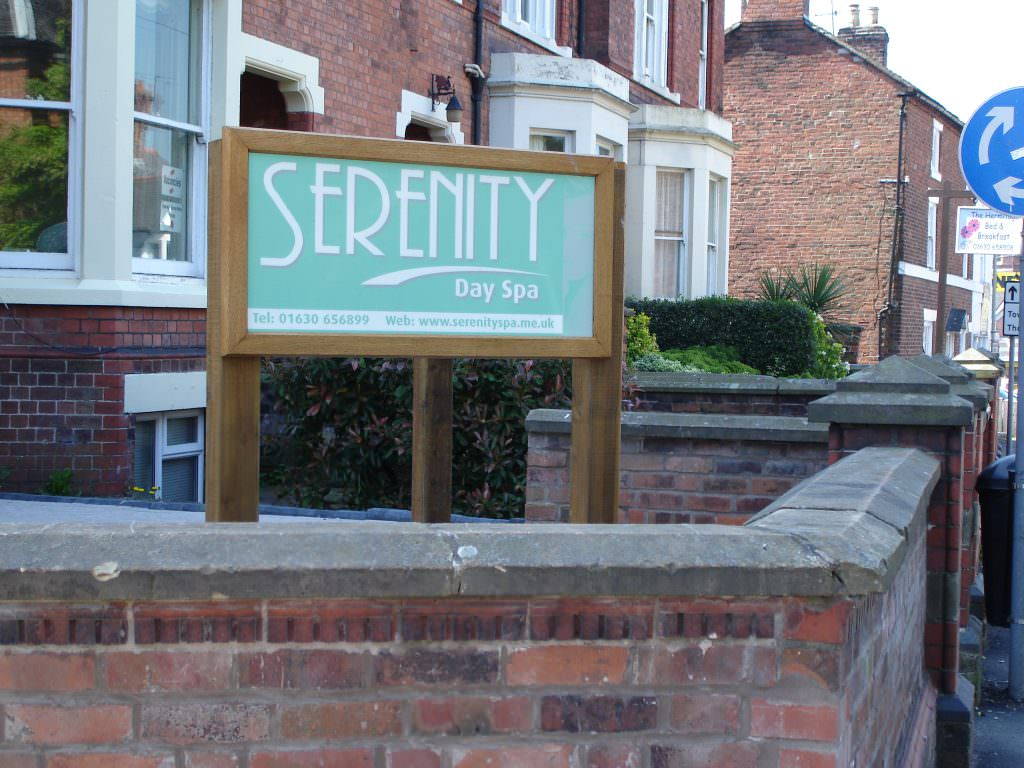 A corporate entrance sign supplied complete with an oak frame and oak posts – positioned outside the office