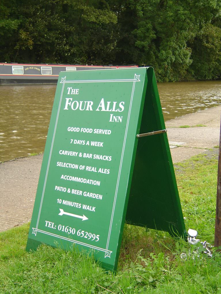 An aluminium Pavement A frame, finished in dark green with white vinyl lettering.  Suitable for promoting local business