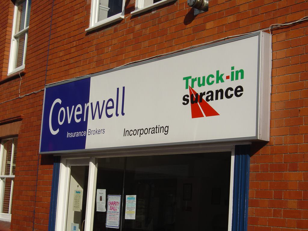 A large illuminated corporate entrance sign with a lighting box.  Full colour graphics and mounted on a brick wall above the shop door