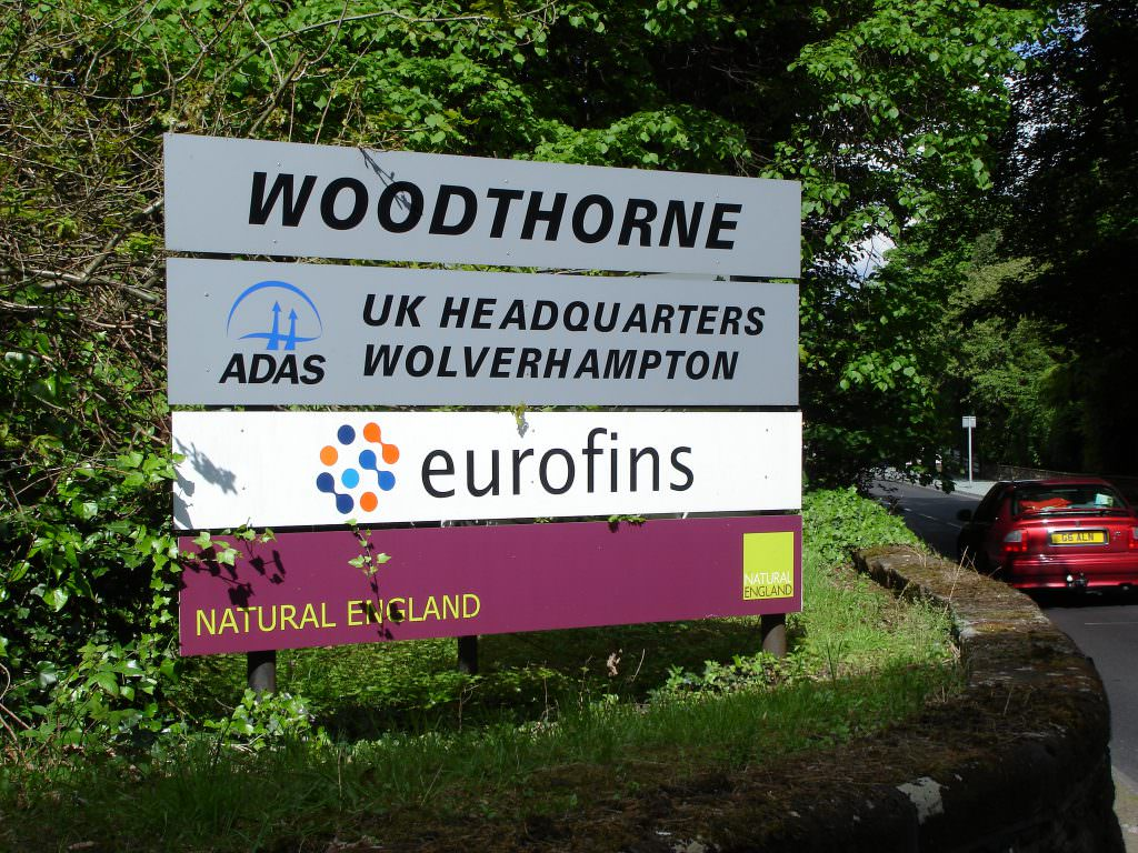 A large corporate entrance sign with posts.  Positoned at the drive entrance & giving names of all the business tenants