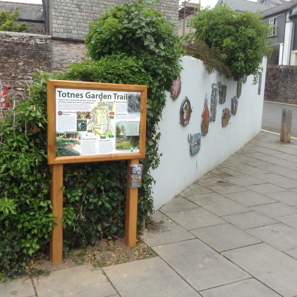 An oak vertical mounted interpretation panel introducing 3 community gardens in the Totnes area. On oak posts and mounted on the edge of a pavement