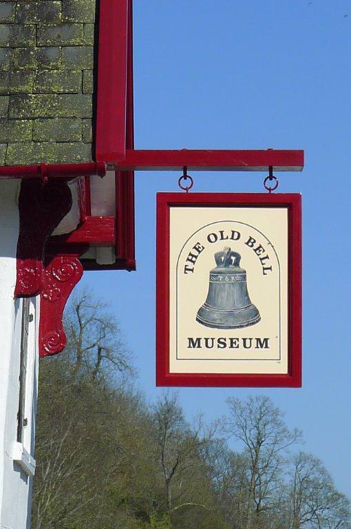 An external and hanging Museum Welcome sign mounted in a timber frame and located above the main entrance door