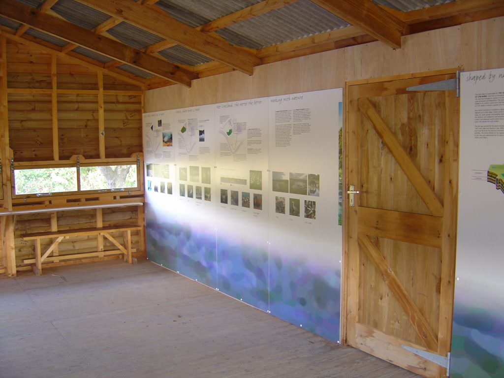 A series of wall mounted information panels in a viewing hide giving details of the commonly visiting species and the associated seasons