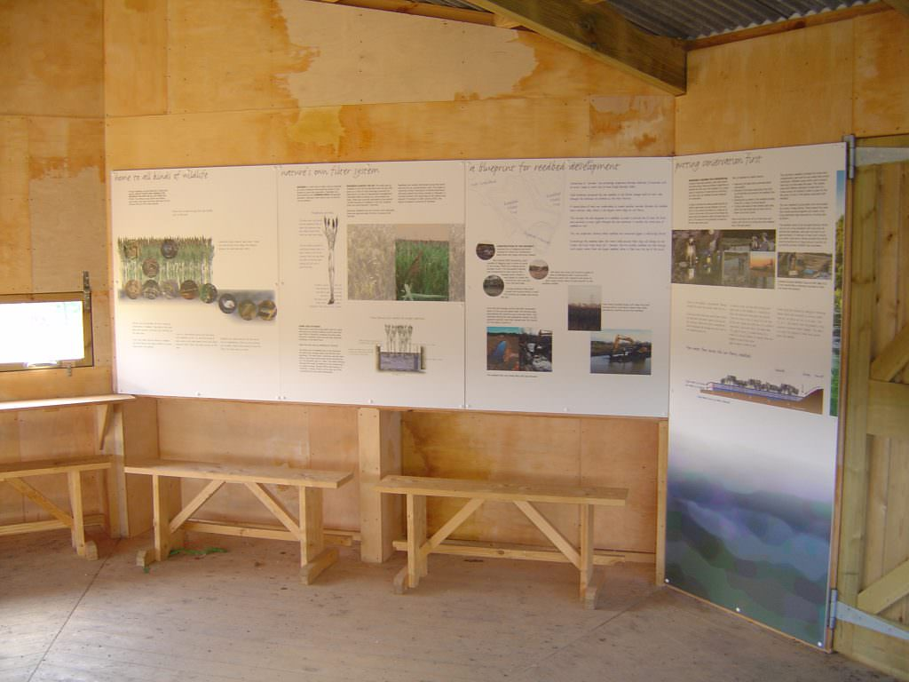 A series of wall mounted interpretation panels in a viewing hide providing details about the reed bed filtration system