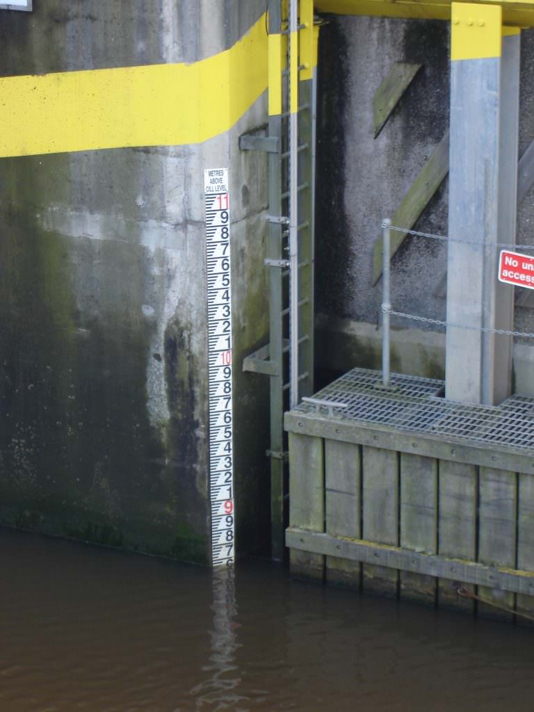 A freshwater D50 gauge board showing a water height of 8.6m and including a Metres Above Cil level plaque at the top. Wall mounted.