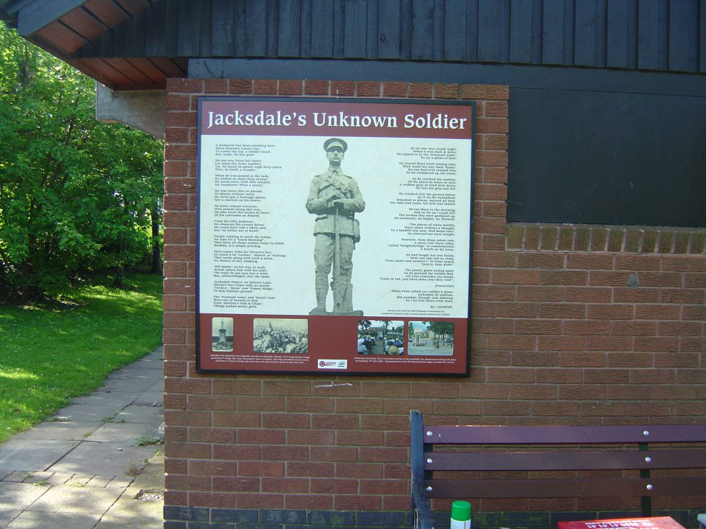 A history themed interpretation panel explaining Jacksdale's Unknown Soldier memorial. The sign is wall mounted in an aluminium frame.