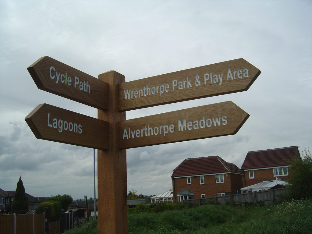 Close up of an oak finger post with 4 directional arms. The name of each destination is routed into the arm and painted white