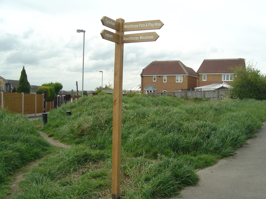 An oak finger post with a tall oak post to make the directional arms difficult to reach by possible vandals