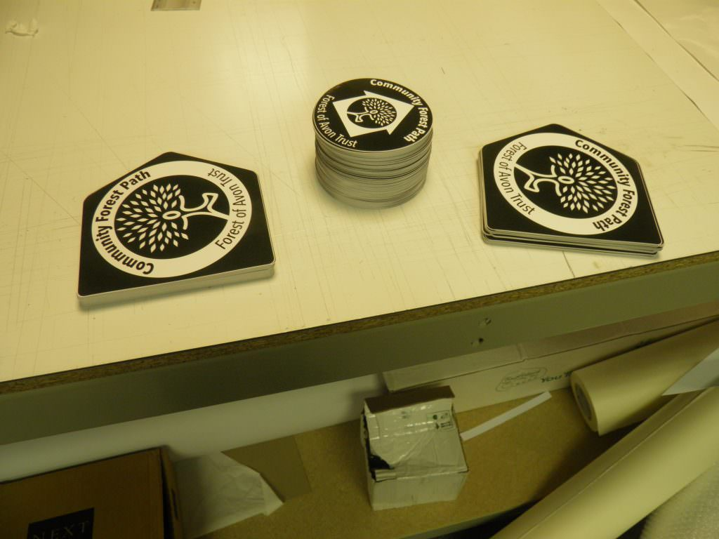 Black on white waymarker discs and directional signs with an arrow shape. Photographed in Shelley Signs factory