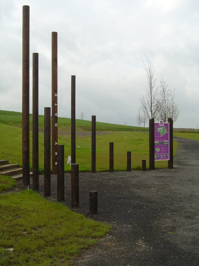 A site entrance feature consisting of a series of round posts, set in a open V formation and with Welcome text to decorate the posts
