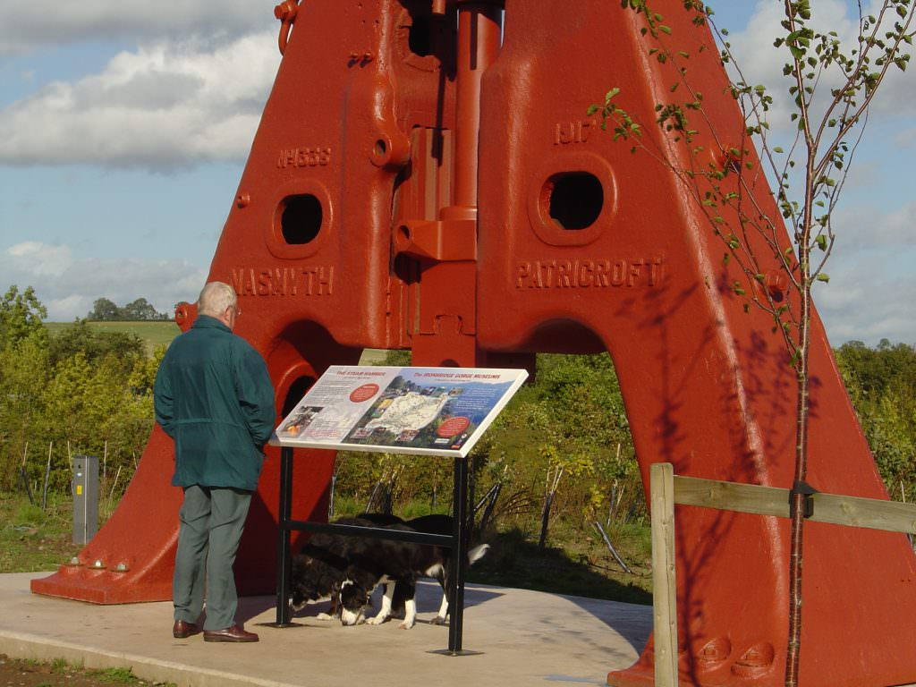 A visitor with his dog reading a heritage themed interpretation panel which is mounted in a steel lectern frame. Part of a steam hammer make a dramatic backdrop