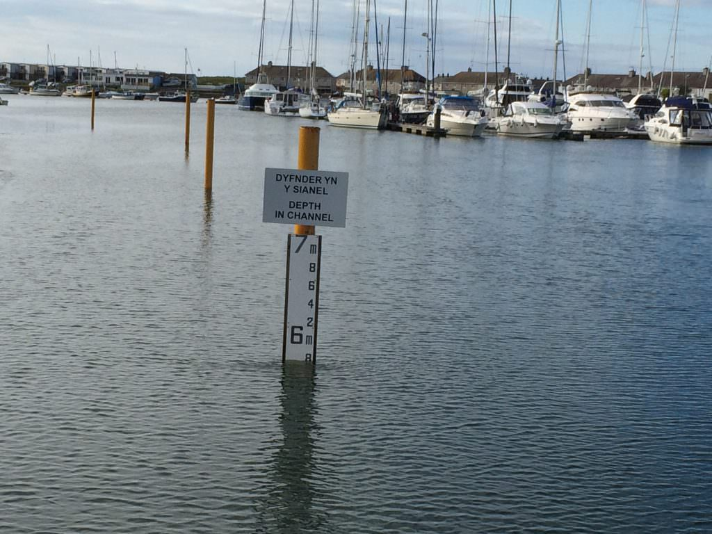 A D53 tidal gauge board shown at high tide in Pwllheli Marina. Mounted on a steel post with a Depth in Channel sign at the top – plenty of water at 5.8m