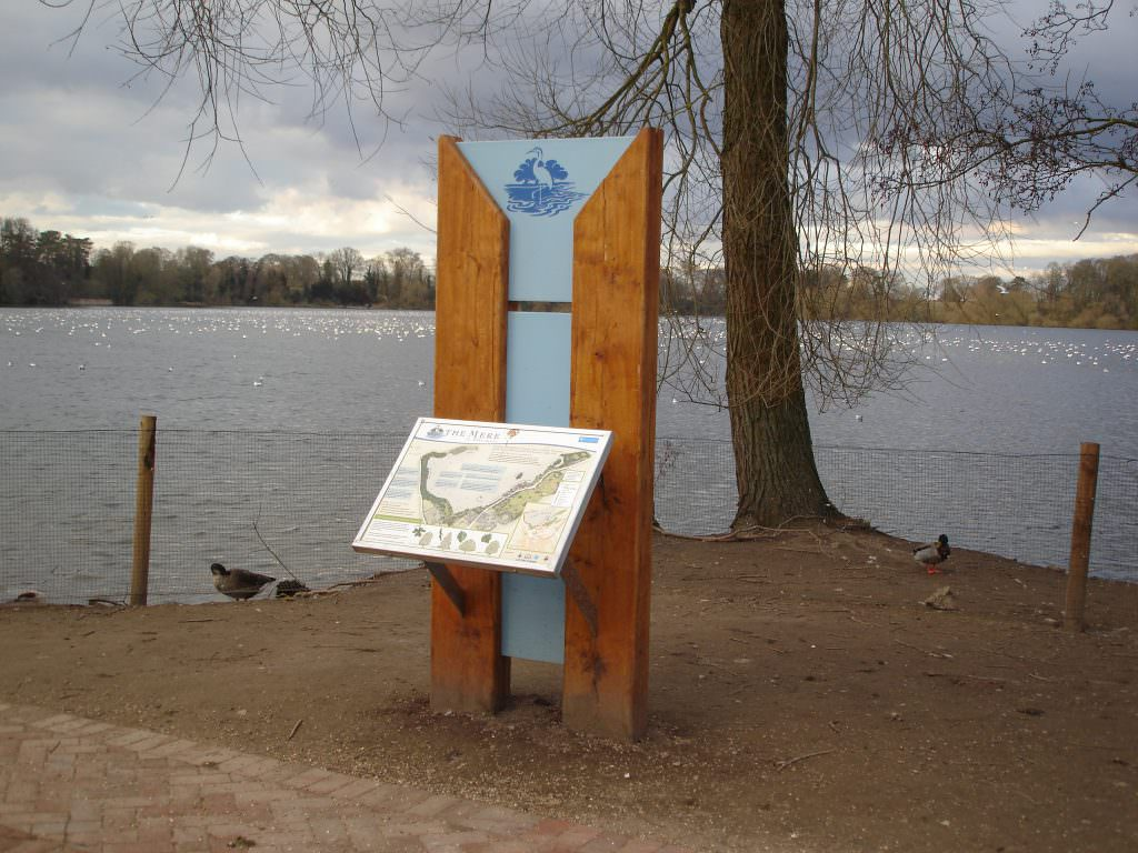 An interpretation panel set by the Mere is Ellesmere. The sign is mounted on substantial oak vertical posts with a central coloured background