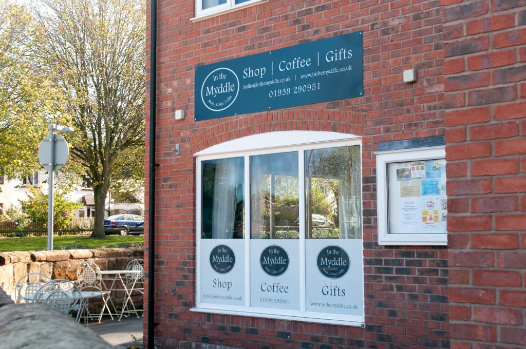 A shop and café sign positioned on a brick wall above the window.  One way vision vinyl fitted to the bottom of the windows