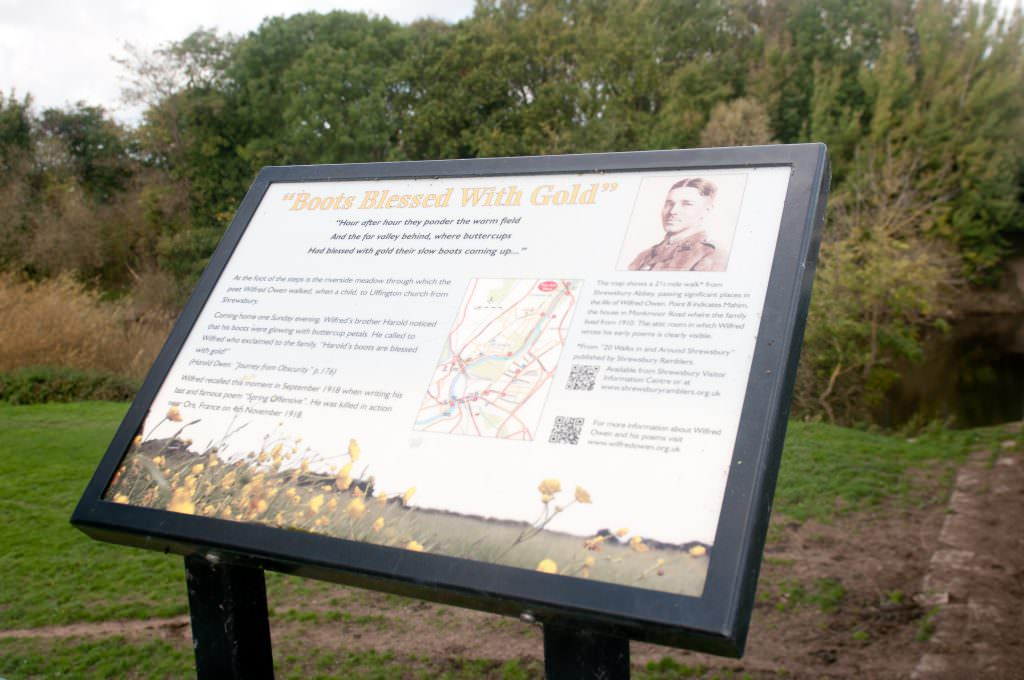 A rural interpretation panel mounted in an aluminium lectern frame, near a river. Introducing a 4 mile walk in honour of Wilfred Owen.