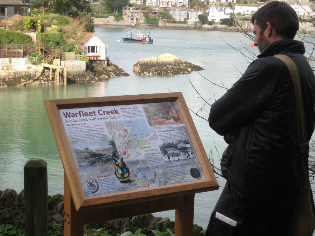 An oak lectern framed interpretation panel set above Warfleet Creek . The man reading the sign learns about the area in war time, peace time & the pottery industry.