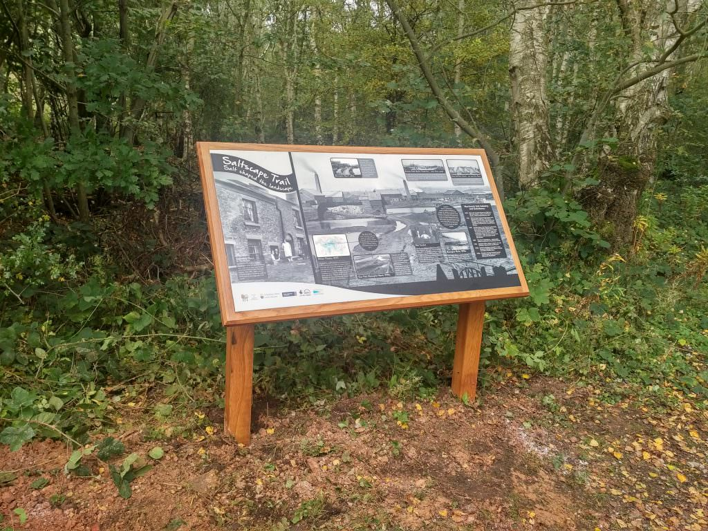 A dramatic rural interpretation sign in an Oak lectern frame. The design consists of old black & white photographs showing how salt shaped the landscape