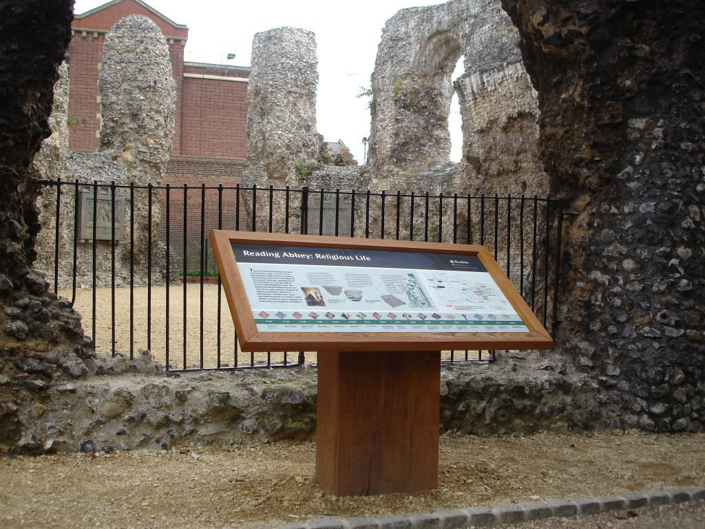 An oak framed interpretation panel introducing Religious Life at Reading Abbey. Set in the ruins of the Abbey with a dramatic historical backdrop.