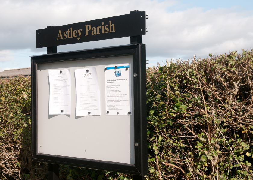 An A1 size aluminium notice board to display 8 sheets of A4 with header panel and posts. Located in a layby of a rural village.