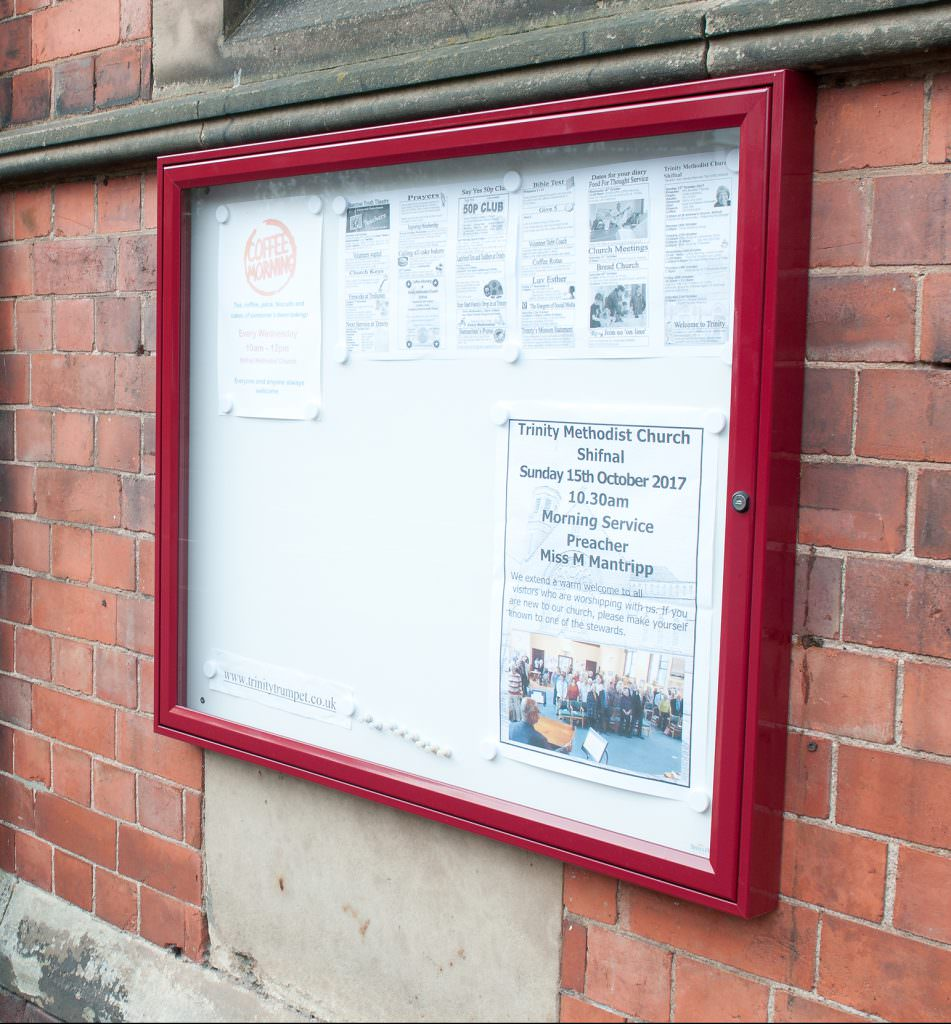 A wall mounted aluminium notice board to display temporary information. Positioned outside a Methodist Church.
