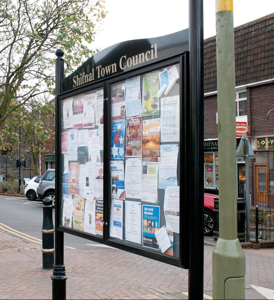 A large double sided notice board with twin doors on each side. Aluminium and with decorative posts and header panel.