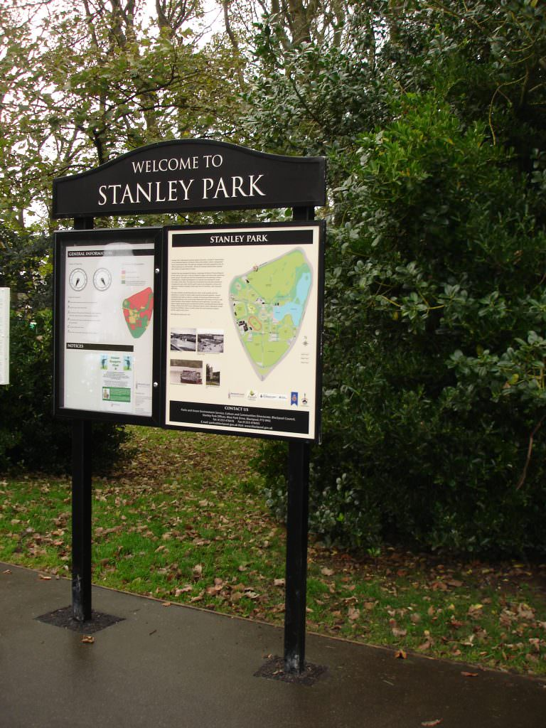 An urban park entrance sign with a printed map panel, lockable notice board incorporating a clock face for opening times, a header panels & posts
