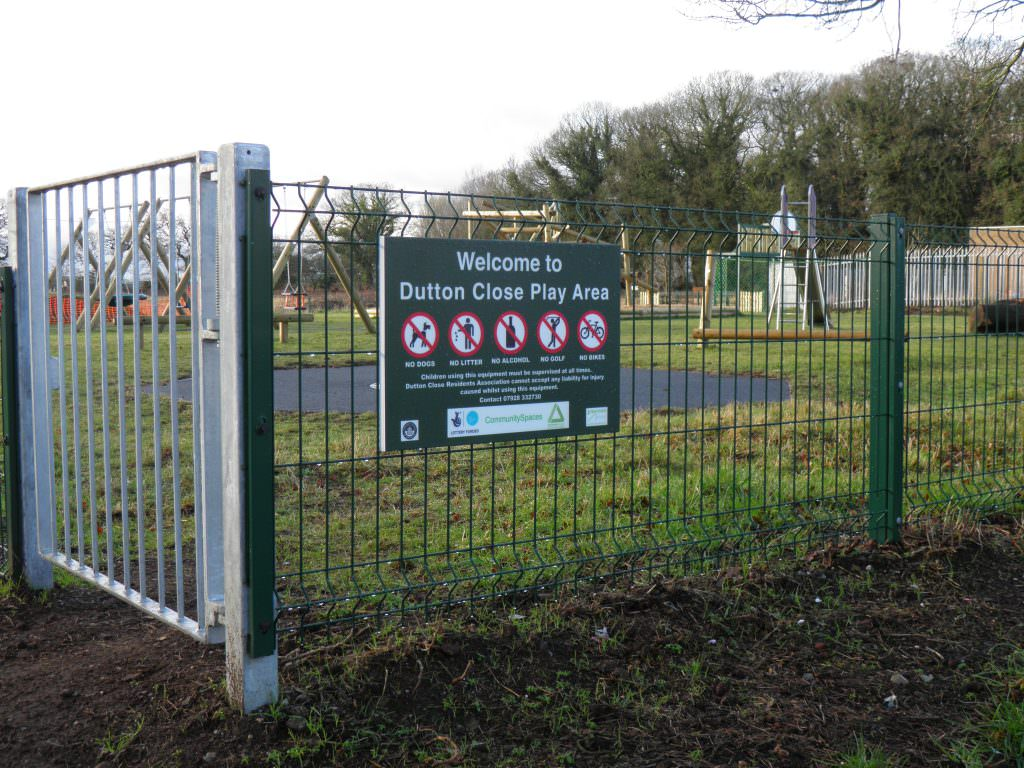 A Welcome sign to an urban play area which is fixed to metal railings. A welcome message, contact details and prohibition symbols
