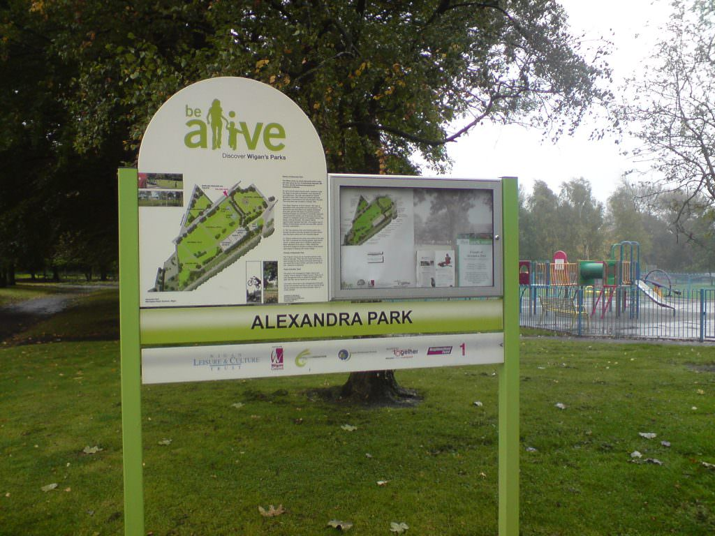 Entrance sign to a large urban park with side mounted posts, a large main sign with a park map, two lower planks with contact details and a lockable notice board