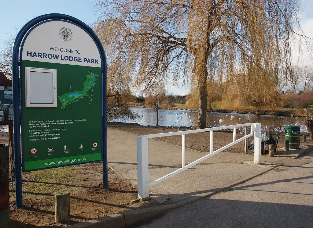 An urban or city park entrance sign mounted in a tubular metal frame structure. A map of the park, contact details and a small lockable notice board.