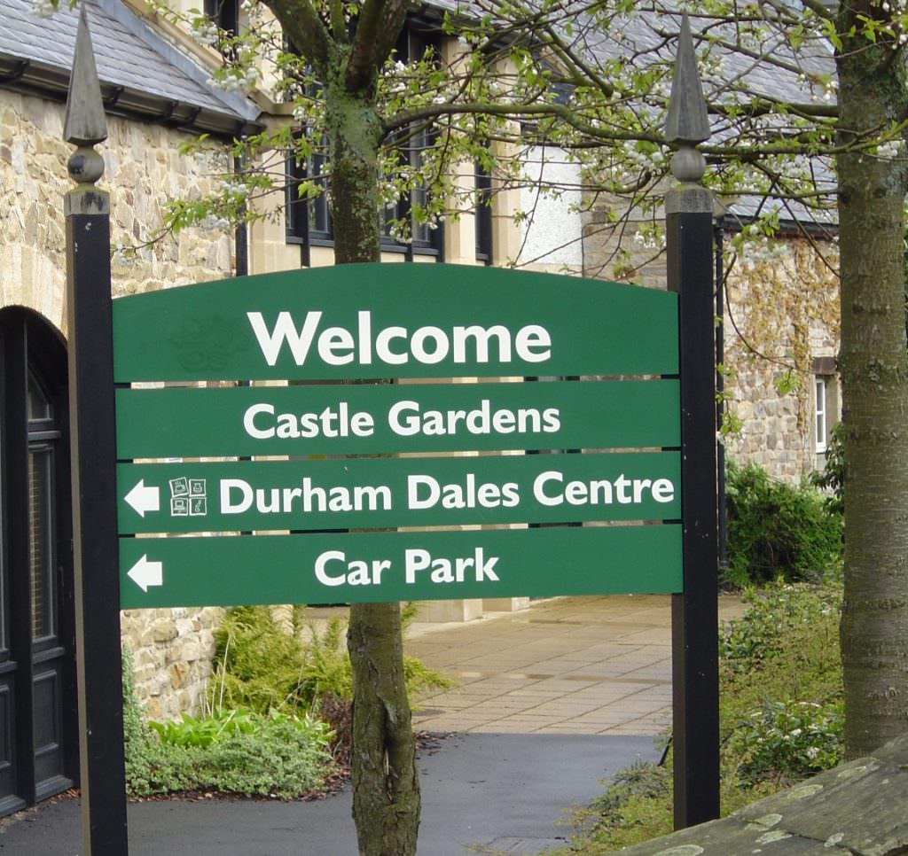 A Welcome sign to a visitor attraction consisting of 4 individual planks. Mounted on timber posts with post finials