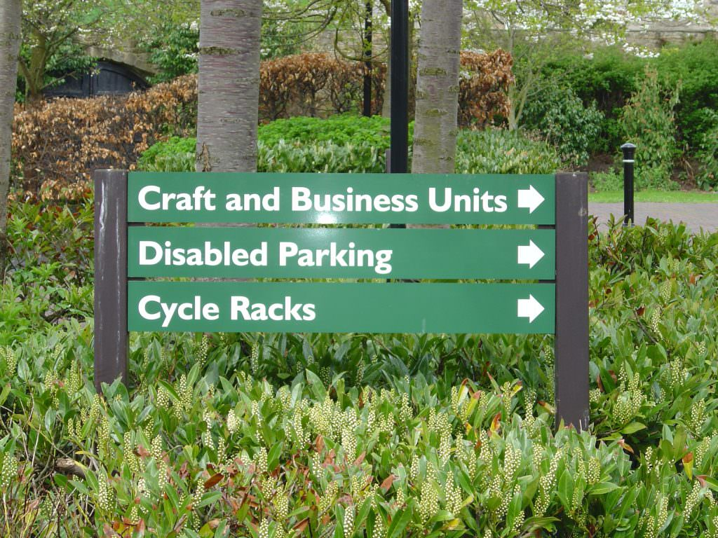 A directional park sign with 3 individual planks to guide visitors around the park. Mounted on timber posts