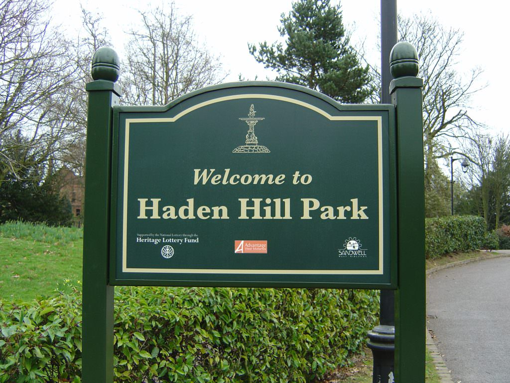 An urban park entrance sign with a simple Welcome to message. Mounted on side mounted posts, with a peaked top and acorn finials.