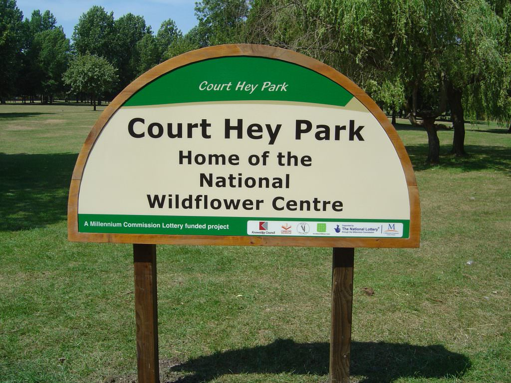 A rural park entrance sign mounted in a timber frame and with softwood posts. A simple Welcome to message with the sign having a semi circular top