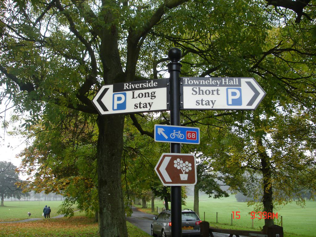 A metal finger post sign on the drive up to an urban park with fingers directing to short and long stay car parks. Produced in aluminium.