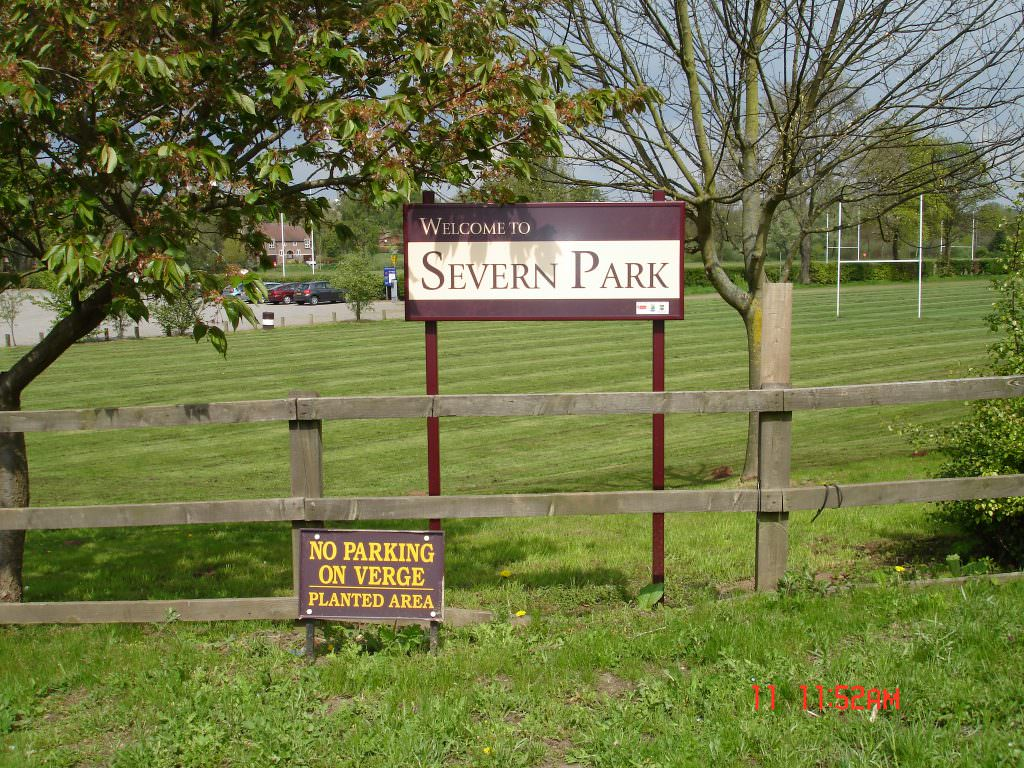 A rural park entrance sign set on the edge of playing fields. A welcome to Severn Park message with aluminium frame & posts