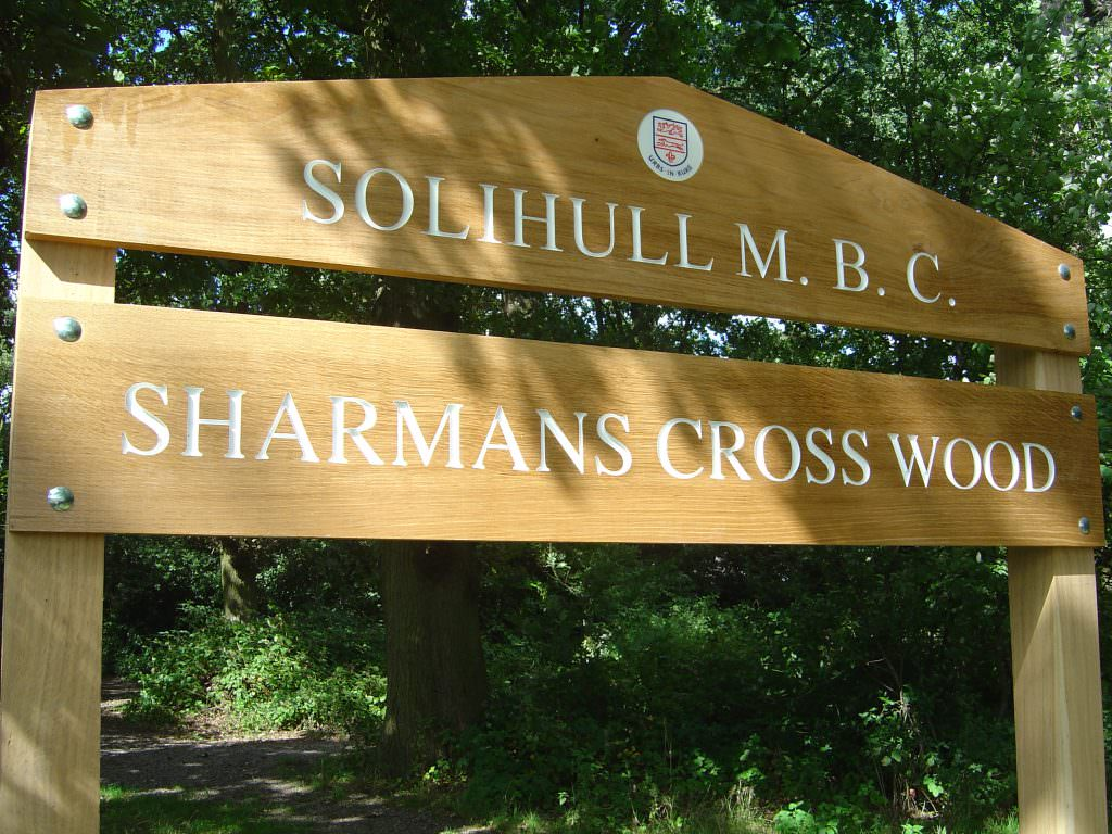 A routed oak park entrance sign with 2 planks. Mounted on oak posts. The text on both planks is indented and painted white.