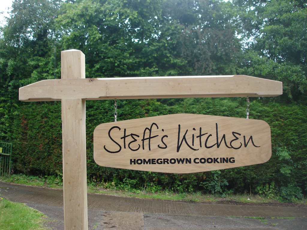 A routed oak hanging sign with indented text, painted black.   Supplied with a hangman style oak frame and chain.