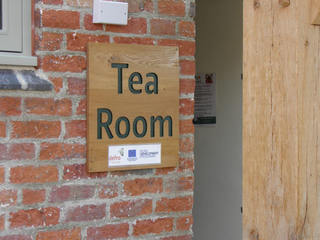 A wall mounted routed oak sign reading Tea Room with the text painted black.  Wall mounted at a visitor attraction.