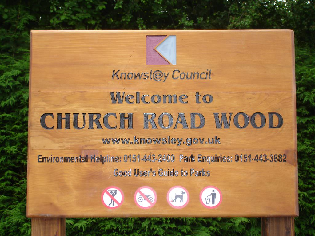 A Park entrance sign produced in routed Cedar.  The indented text is painted black.  The design includes contact details and prohibition symbols.  Post mounted.