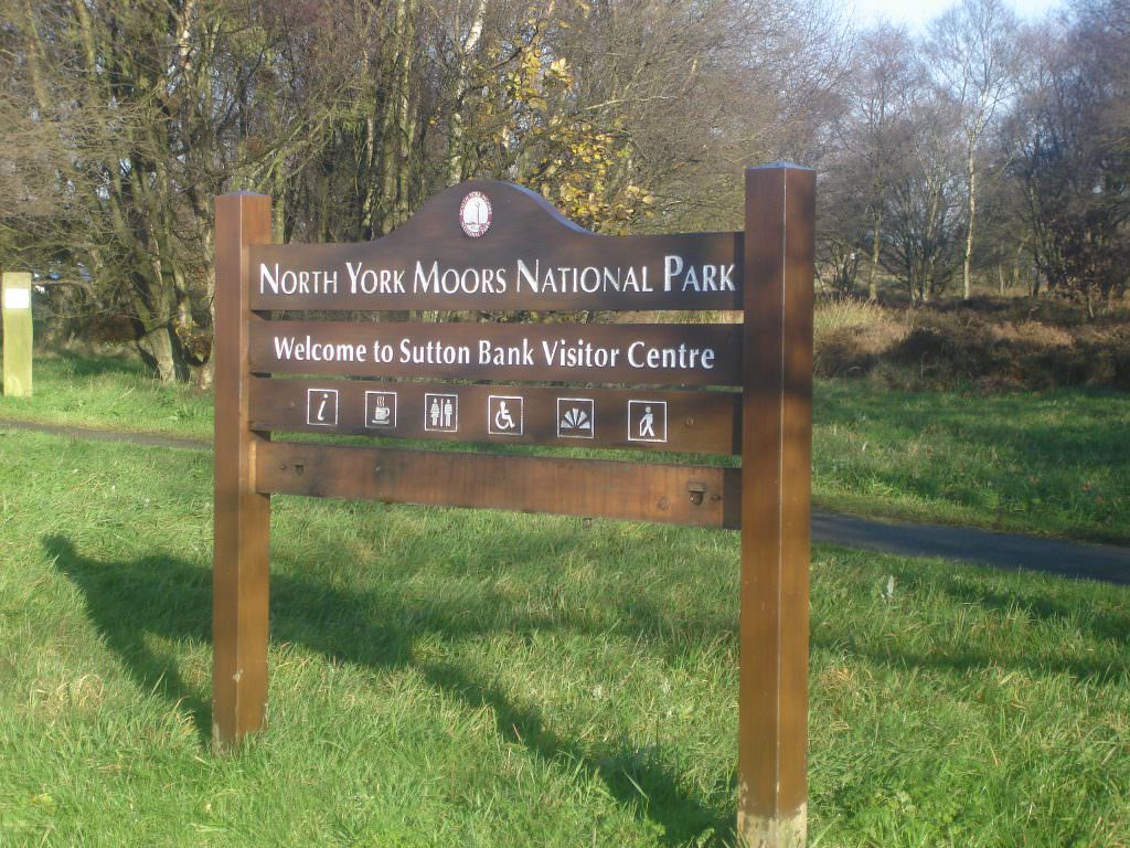 A 4 plank timber entrance sign to a National Park.  Supplied with routed text, painted white and side mounted posts.