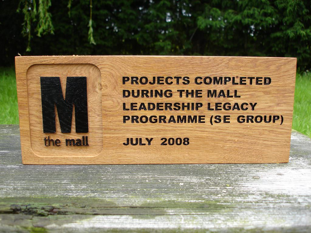A routed oak legacy plaque with both indented and raised text, painted black