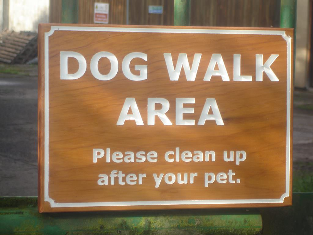 A very simple routed Cedar sign, with painted and indented lettering.  Post mounted.  Providing Dog control information.