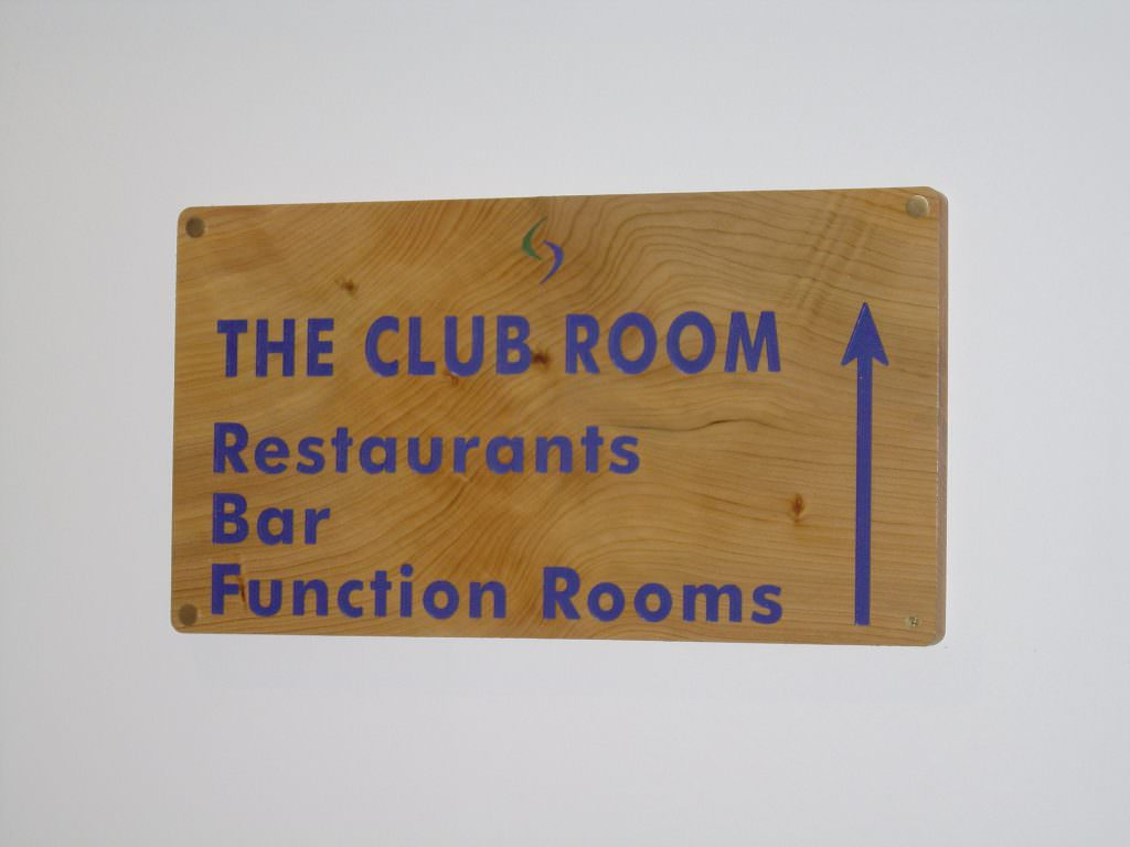 An internal club house sign produced in routed timber with indented text.  Text painted blue and wall mounted.