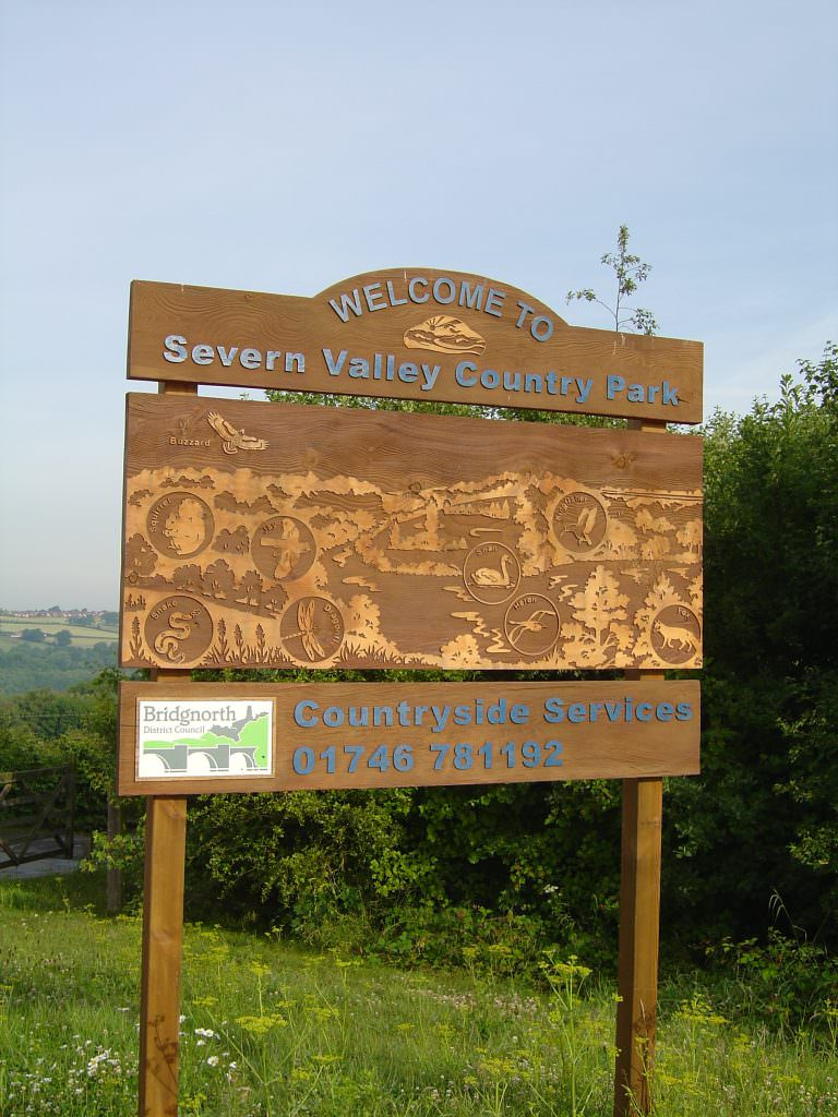 A large park entrance sign produced in sandblasted cedar.  The main design includes a complex scenic collage featuring the view and species of interest.