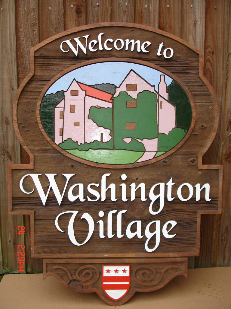 A village entrance sign produced in sandblasted Cedar.  The sign in shaped like a shield with the design including colour picture.  Post mounted.